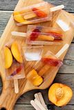 Peach iced tea popsicles, on paddle board against rustic wood Royalty Free Stock Photos
