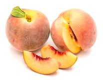 Peach isolated on white. One whole peach with green leaf, cut open, two slices, isolated on white background Royalty Free Stock Photography