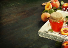 Peach jam with fresh peaches on table Stock Images