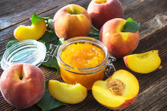 Peach jam and fresh peaches Stock Photos