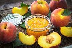 Peach jam and fresh peaches Stock Images