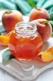 Peach jam. In glass jar on white wooden background stock photography