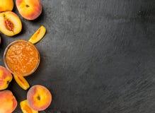 Some Peach Jam on a dark slate slab. Peach Jam on a vintage slate slab as detailed close-up shot; selective focus stock photography