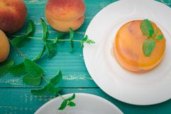 Peach jelly with mint close up. Wooden turquoise background. Top view royalty free stock photo