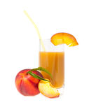 Peach juice. In a glass nearby a peach with foliage idly Stock Images