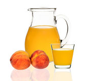 Peach juice in a glass and carafe Stock Photos