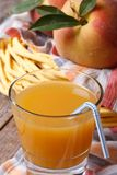 Peach juice in glass closeup on a background of fruit Stock Image