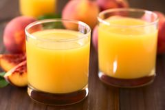 Peach Juice or Nectar. In glasses with fresh ripe peach fruits in the back, photographed on dark wood with natural light Selective Focus, Focus on the front of Royalty Free Stock Images