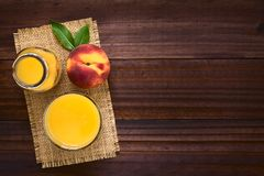 Peach Juice or Nectar. In glass and in bottle with fresh ripe peach fruit on the side, photographed overhead on dark wood with natural light Selective Focus Stock Photo