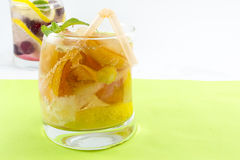 Peach juice with peach slices in a crooked glass on green backgr Royalty Free Stock Photos