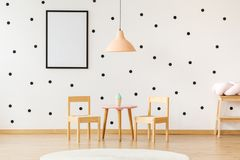 Peach lamp in child`s room. Mockup of poster on dots wallpaper in child`s room with peach lamp above wooden chairs and table with toy royalty free stock images