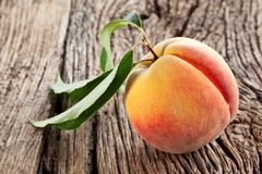 Peach with leaves. On the old wooden table stock image