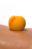 Peach lies at the female body Royalty Free Stock Photos