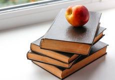 Peach lies on four big black books. Closeup Royalty Free Stock Images