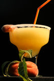 Peach Margarita. With peaches for garnish and orange straw Royalty Free Stock Image