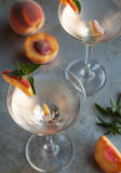Peach Martinis. Refreshing Summer cocktails vodka martinis with fresh peaches Stock Image