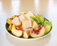 Peach melon sliced basil plate Royalty Free Stock Photos