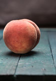 Peach on petrol colored wooden background Stock Images