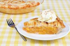 Peach Pie Ala Mode. With vanilla ice cream sprinkled with cinnamon royalty free stock image