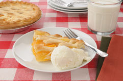 Peach pie ala mode. A slice of peach pie with vanilla ice cream and milk stock photos