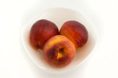 Peach on plate. Some fresh peaches on a plate located on a white background Royalty Free Stock Photos
