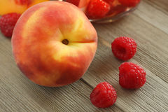 Peach and raspberries. Peach with 3 raspberries on wood background, lit with natural day light Royalty Free Stock Image