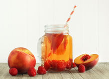 Peach and raspberry drink. On wood background Stock Images