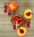 Peach and raspberry drink. With wood background; over head veiw; lit with natural light Stock Image