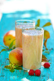 Peach-raspberry milkshake. In glasses on a blue wooden background Royalty Free Stock Photos