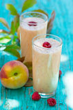 Peach-raspberry milkshake. In glasses on a blue wooden background Stock Photography