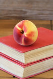 Peach on red books Royalty Free Stock Images