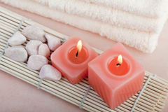 Peach relaxing spa concept. Red candles and stones with peach color background Royalty Free Stock Images