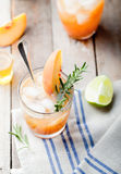 Peach and rosemary fizz cocktail on a wooden background. Cocktail. Stock Image