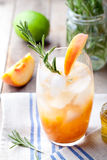 Peach and rosemary fizz cocktail on a wooden background. Cocktail. Stock Images