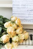Peach roses on the piano stock image