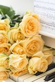 Peach roses on the piano royalty free stock image