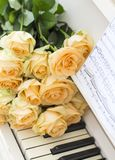 Peach roses on the piano stock photography