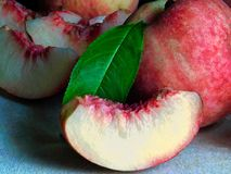 A peach slice with peaches in the background stock photos