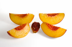 Peach sliced on four and clingstone. Four peach slices and stone on white background Royalty Free Stock Images