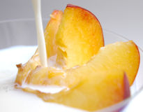 Peach slices with milk II. Pouring milk over peach slices Stock Images