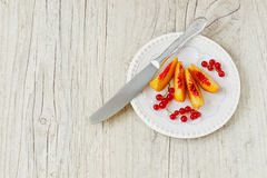 Peach slices and red currants Royalty Free Stock Photography