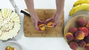 Peach slices on a wooden cutting board. Woman slicing fresh ripe peaches. Arranging fruit platter step by step top view on white background stock video footage