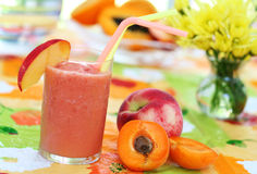 Peach smoothie. Bright, colorful summer table with peach smoothie, tropical fruits, and flowers stock images