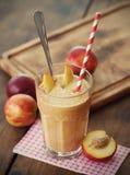 Peach Smoothie. With few peach on table Stock Photos