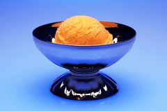 Peach Sorbet. A scoop of peach sorbet in a colorful setting stock images