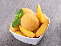 Peach sorbet in bowl. On wooden background Royalty Free Stock Photography