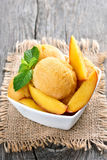 Peach sorbet decorated with mint. In white bowl on rustic table Royalty Free Stock Photography