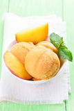 Peach sorbet with fresh fruit slices. And mint in white bowl Stock Photography
