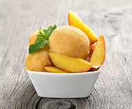 Peach sorbet ice cream. With slices in bowl on wooden background Royalty Free Stock Photos