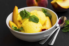 Peach sorbet scoops in a bowl with peach slices and mint. Fresh peach sorbet with peach slices and mint leaves in a bowl Royalty Free Stock Photo